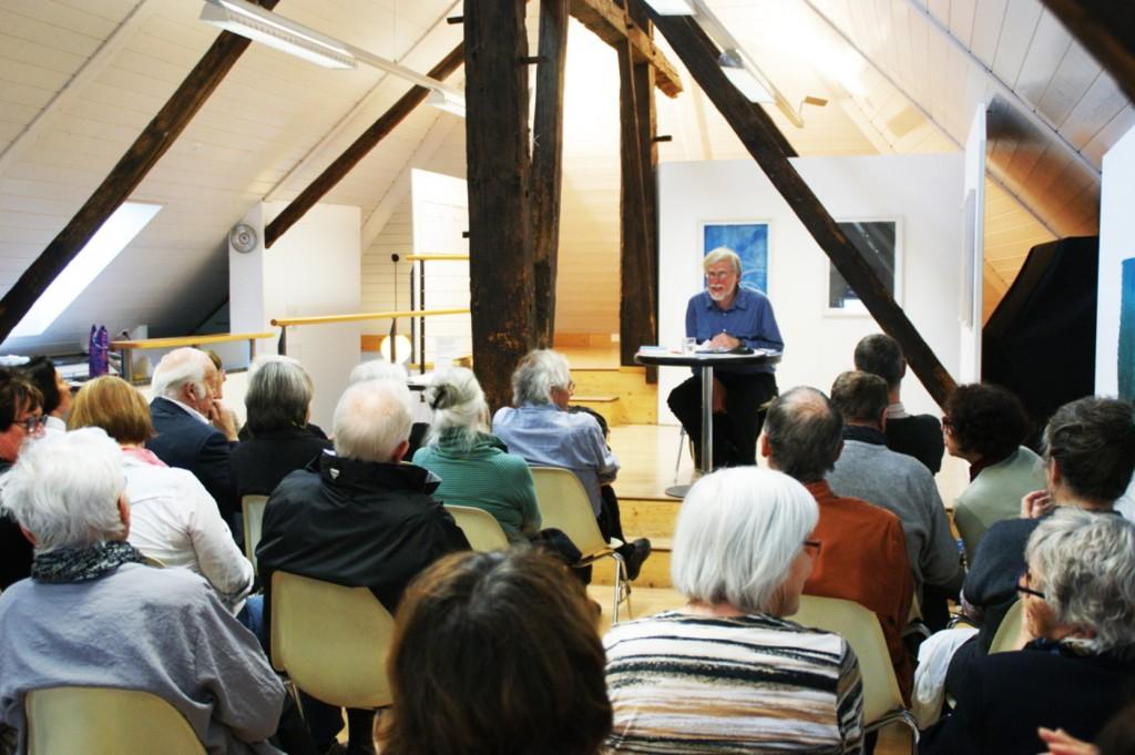 Erhard von Büren an einem Pult am Lesen vor Publikum